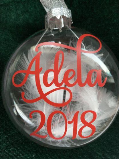 Min første jul julekule med navn og årstall i rød skrift. Pyntet med hvit fjær og bånd i sølv.
