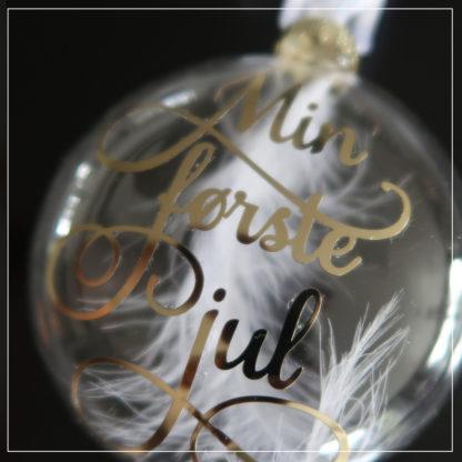 """Nærbilde av julekule med teksten """"min første jul"""""""