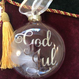 Bilde av julekule med teksten God Jul og personlig navn på andre siden. Julekulen er dekorert med fjær og hvitt silkebånd.