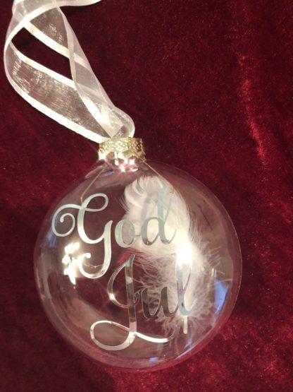 Bilde av julekule i glass med teksten God Jul. Julekulen er pyntet med hvite fjær inni og hvitt silkebånd.