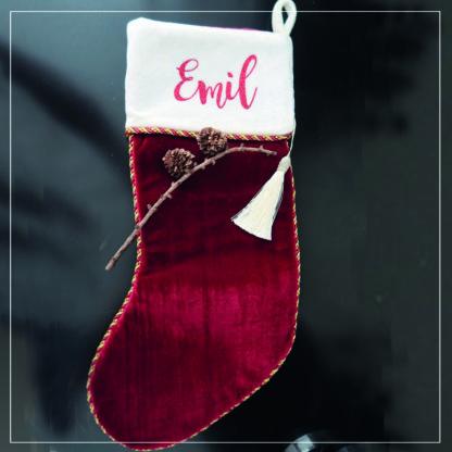 Rød julestrømpe med navnetrekk på hvit mansjett