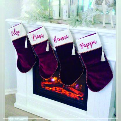 Fire julestrømper med navn hengende på en peishylle
