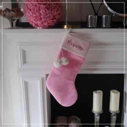 Rosa julestrømpe på peishylle