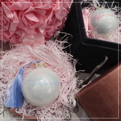 To hvite julekuler med navn i rosa og blått