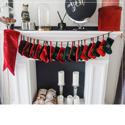 24 små julestrømper i grønt og rødt hengende på en peishylle med broderte adventstall