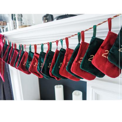 nærbilde av 24 julestrømper med broderte tall hengende på et bånd